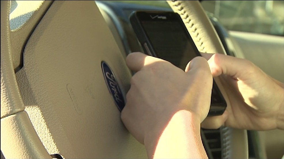 distracted driving holding phone at wheel.jpg