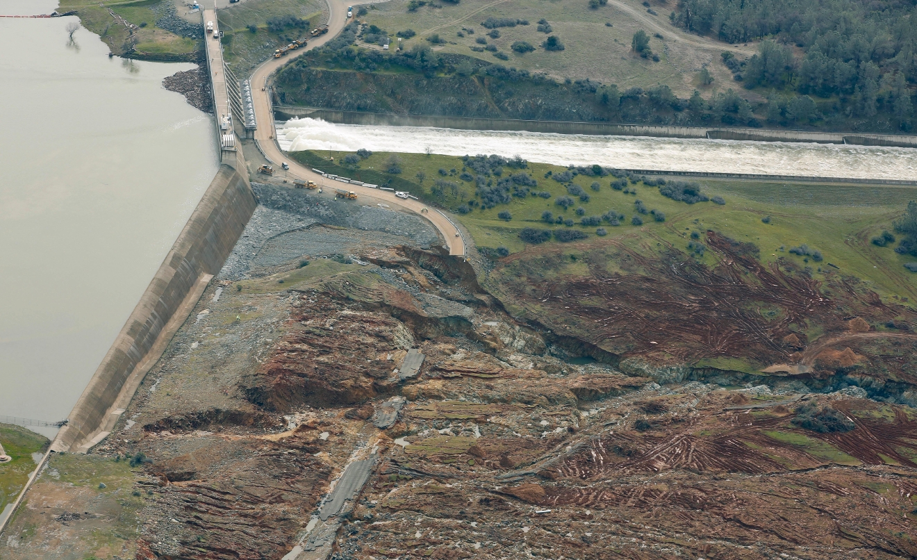 Erosion caused when overflow water cascaded down the emergency spillway, bottom, is seen as water continues to flow down the main spillway, top, of the Oroville Dam, Monday, Feb. 13, 2017, in Oroville, Calif. The water level dropped Monday at the nation's tallest dam easing slightly the fears of a catastrophic spillway collapse that prompted authorities to order people to leave their homes downstream. (AP Photo/Rich Pedroncelli)