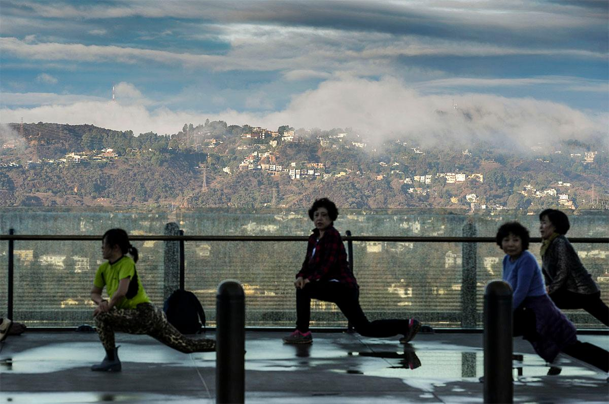 The last clouds and low lying fog roll over the foothills above Los Angeles Monday morning, Nov.21, 2016, as women do their morning workouts at Griffith Observatory. An overnight storm dropped more than an inch of rain in some areas. (David Crane/Los Angeles Daily News via AP)