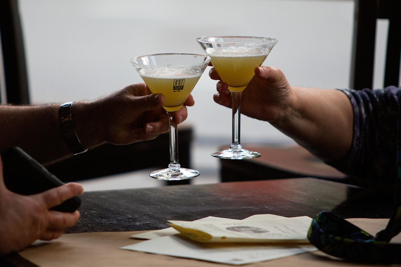 Patrons of Tini Bigs Lounge clink their drinks during the bar's final day of business after serving the Seattle community for over 20 years. (Sy Bean / Seattle Refined)