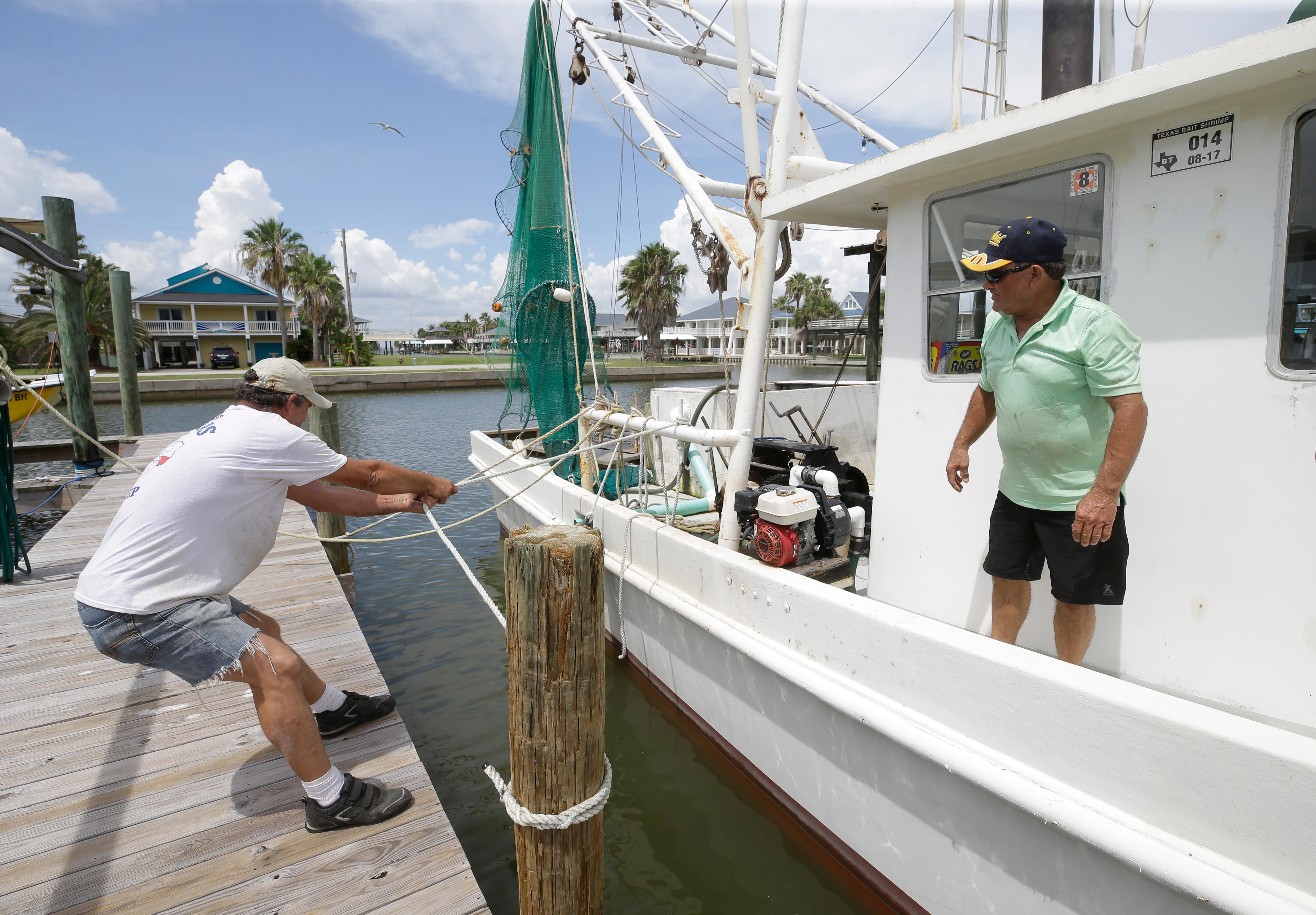 Steve Elliott, left, and David Prater, right, secure a 40-foot shrimp boat at West End Marina, Thursday, Aug. 24, 2017, in Galveston, Texas, as people prepare for Hurricane Harvey. (Melissa Phillip/Houston Chronicle via AP)
