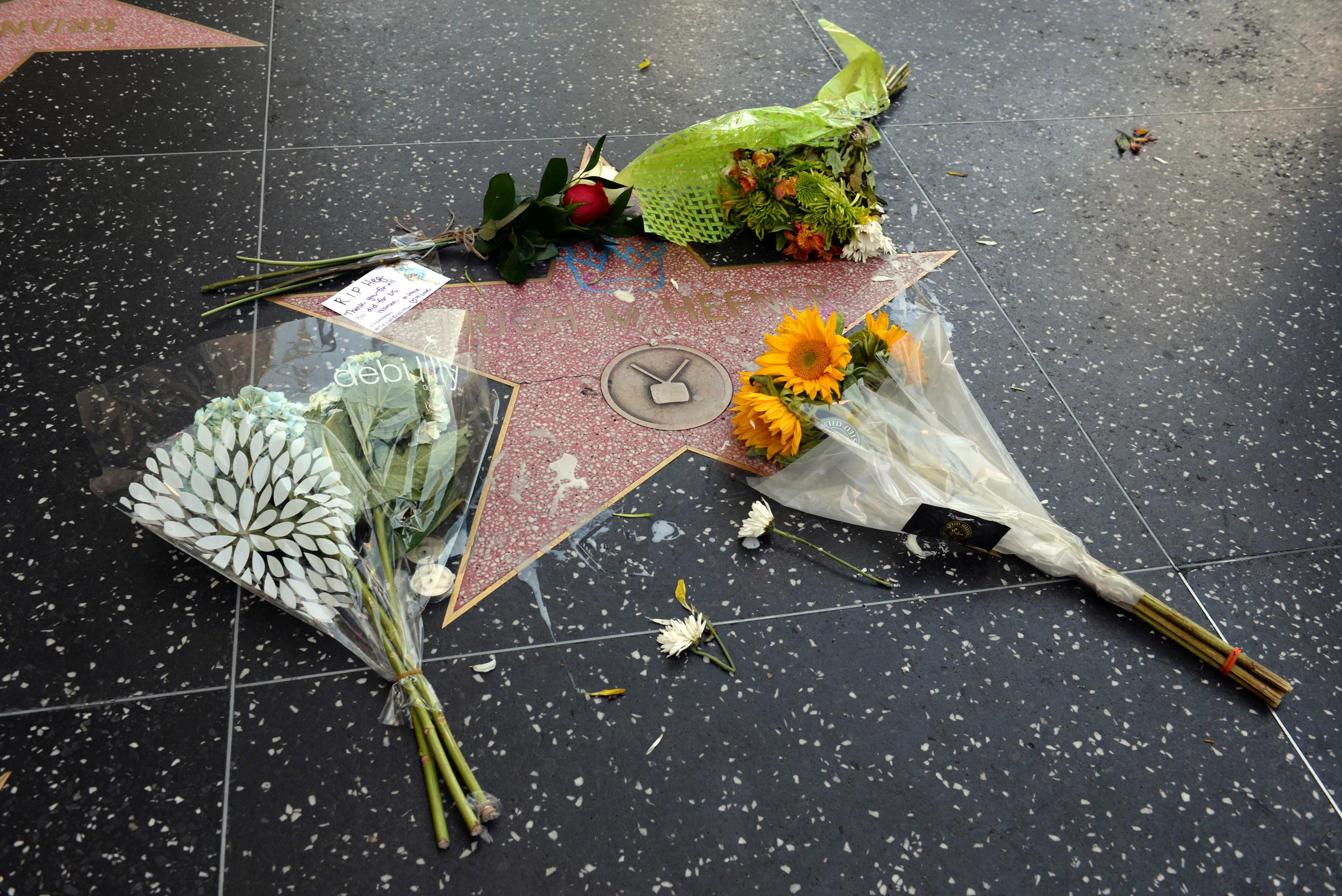 Flowers are placed on Hugh Hefner's star on the Hollywood Walk of Fame Thursday, Sept. 28, 2017 in Los Angeles.  Hefner died of natural causes at his home on Wednesday at the age of 91. (AP Photo/Axel Koester)