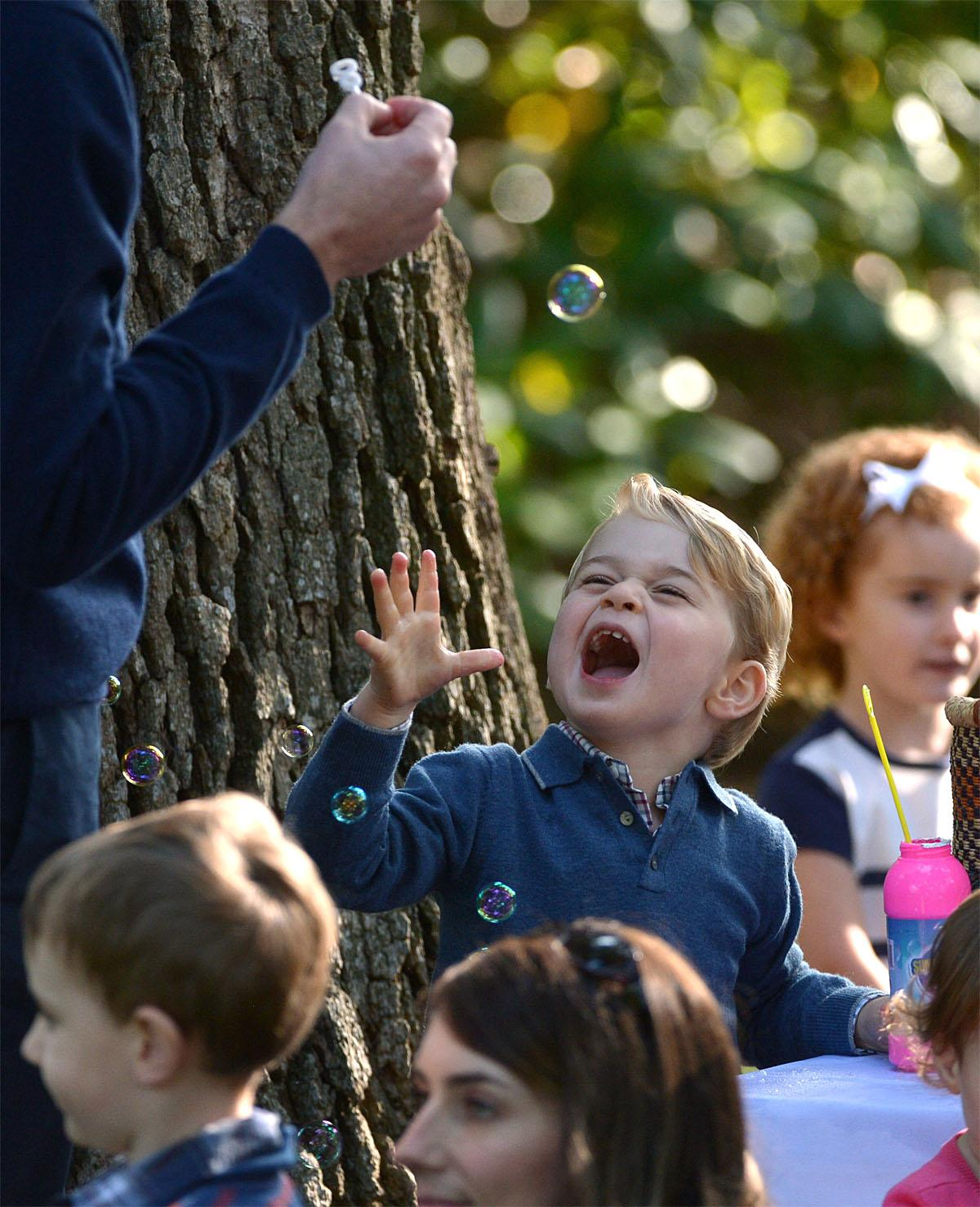 Britain's Prince George plays with bubbles during a children's tea party at Government House in Victoria, British Columbia Thursday, Sept. 29, 2016. (Jonathan Hayward/The Canadian Press via AP)