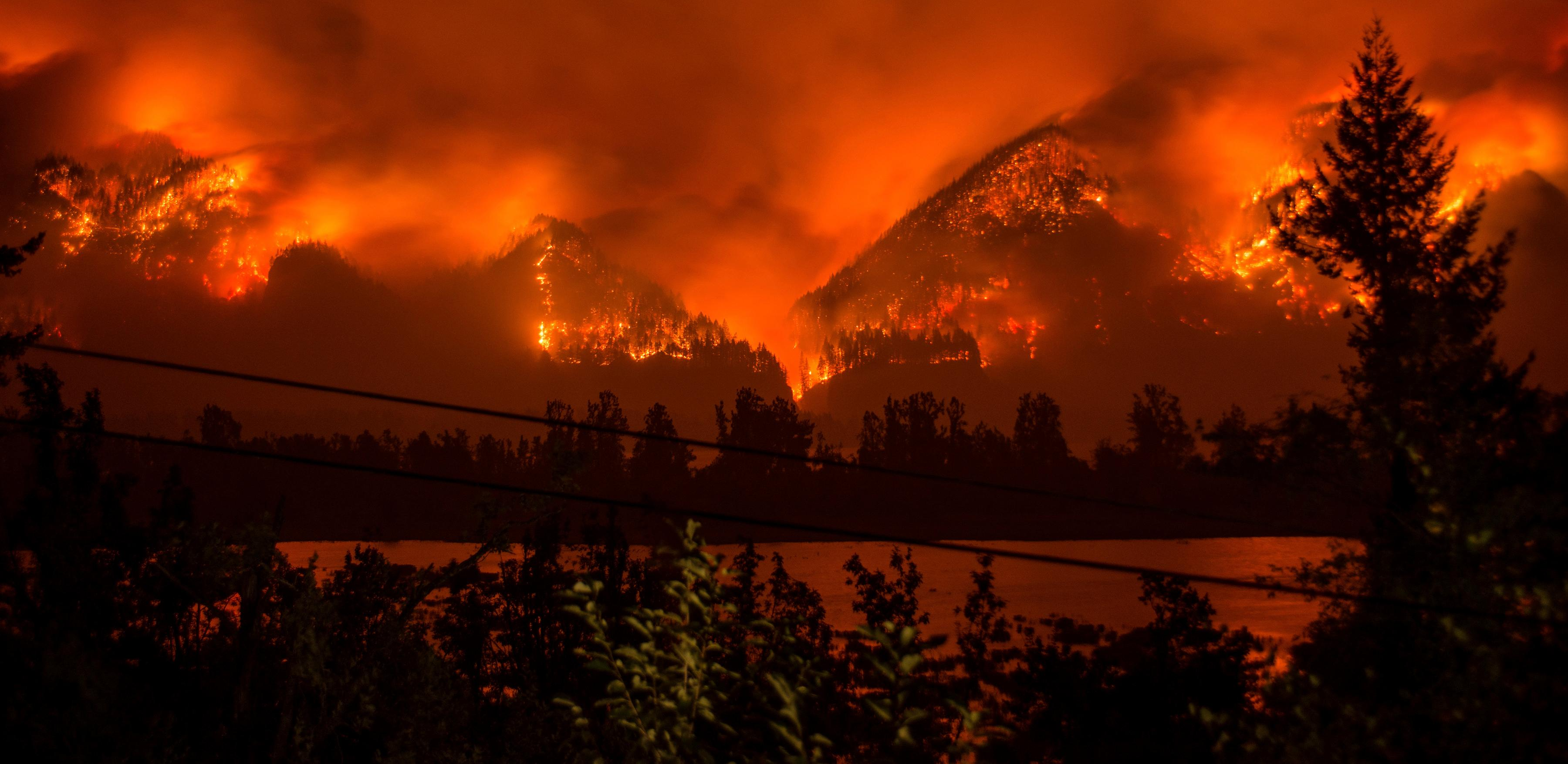 FILE--This Monday, Sept. 4, 2017, file photo provided by KATU-TV shows a wildfire as seen from near Stevenson Wash., across the Columbia River, burning in the Columbia River Gorge above Cascade Locks, Ore. The fast-moving wildfire chewing through Oregon's Columbia River Gorge is threatening more than homes and people. It's also devouring the heart of the state's nature-loving identity. (Tristan Fortsch/KATU-TV via AP, file)