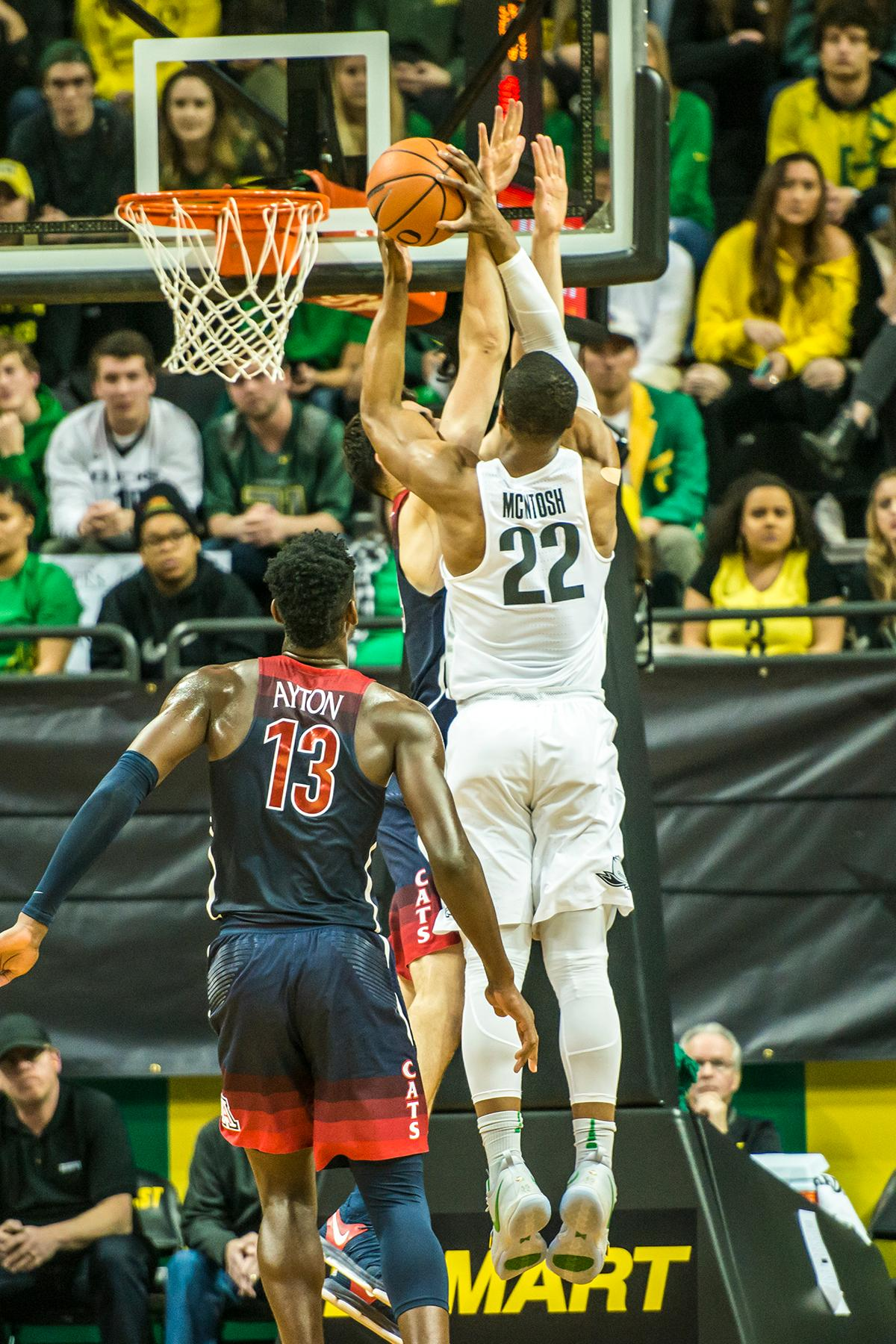 Oregon's MiKyle McIntosh goes up over Arizona defenders in their matchup at Matthew Knight Arena Saturday. The Ducks upset the fourteenth ranked Wildcats 98-93 in a stunning overtime win in front of a packed house of over 12,000 fans for their final home game to improve to a 19-10 (9-7 PAC-12) record on the season. Oregon will finish out regular season play on the road in Washington next week against Washington State on Thursday, then Washington on the following Saturday. (Photo by Colin Houck)