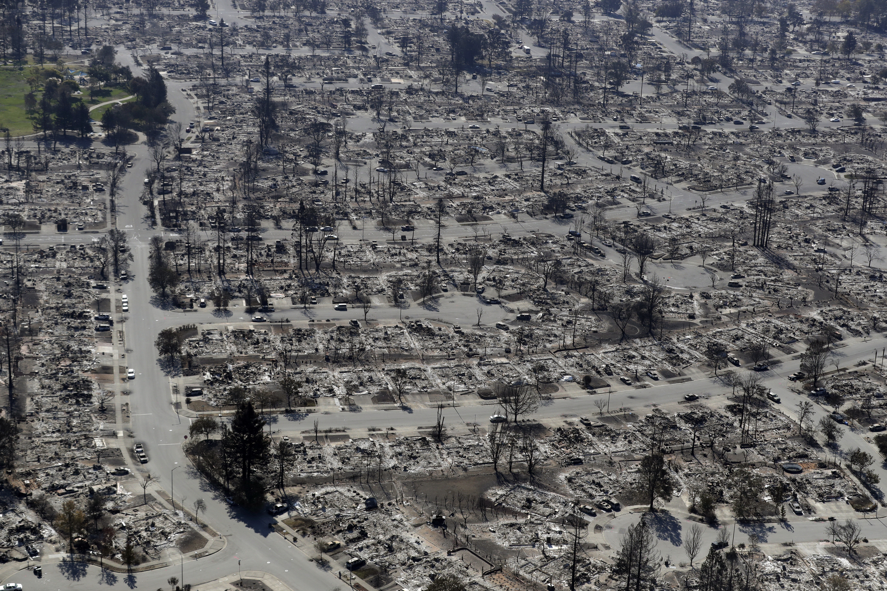 FILE - In this Oct. 14, 2017, file photo, an aerial view shows the devastation of the Coffey Park neighborhood after a wildfire swept through in Santa Rosa, Calif. California's insurance commissioner said Tuesday, Oct. 31, 2017 that losses from a series of destructive wildfires now exceed $3.3 billion.  (AP Photo/Marcio Jose Sanchez, File)