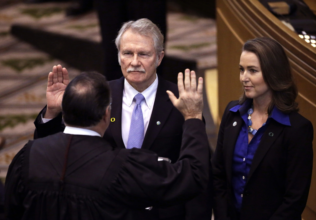 FILE - In this Jan. 12, 2015 file photo, Oregon Gov. John Kitzhaber, center, is joined by his fiancee, Cylvia Hayes, as he is sworn in for an unprecedented fourth term by Senior Judge Paul J. De Muniz in Salem, Ore. A U.S. House committee has found former Gov. Kitzhaber and a federal agency mishandled the creation of Oregon's health insurance enrollment website, with the Democratic governor's political advisers making decisions based on his re-election campaign. (AP Photo/Don Ryan, File)