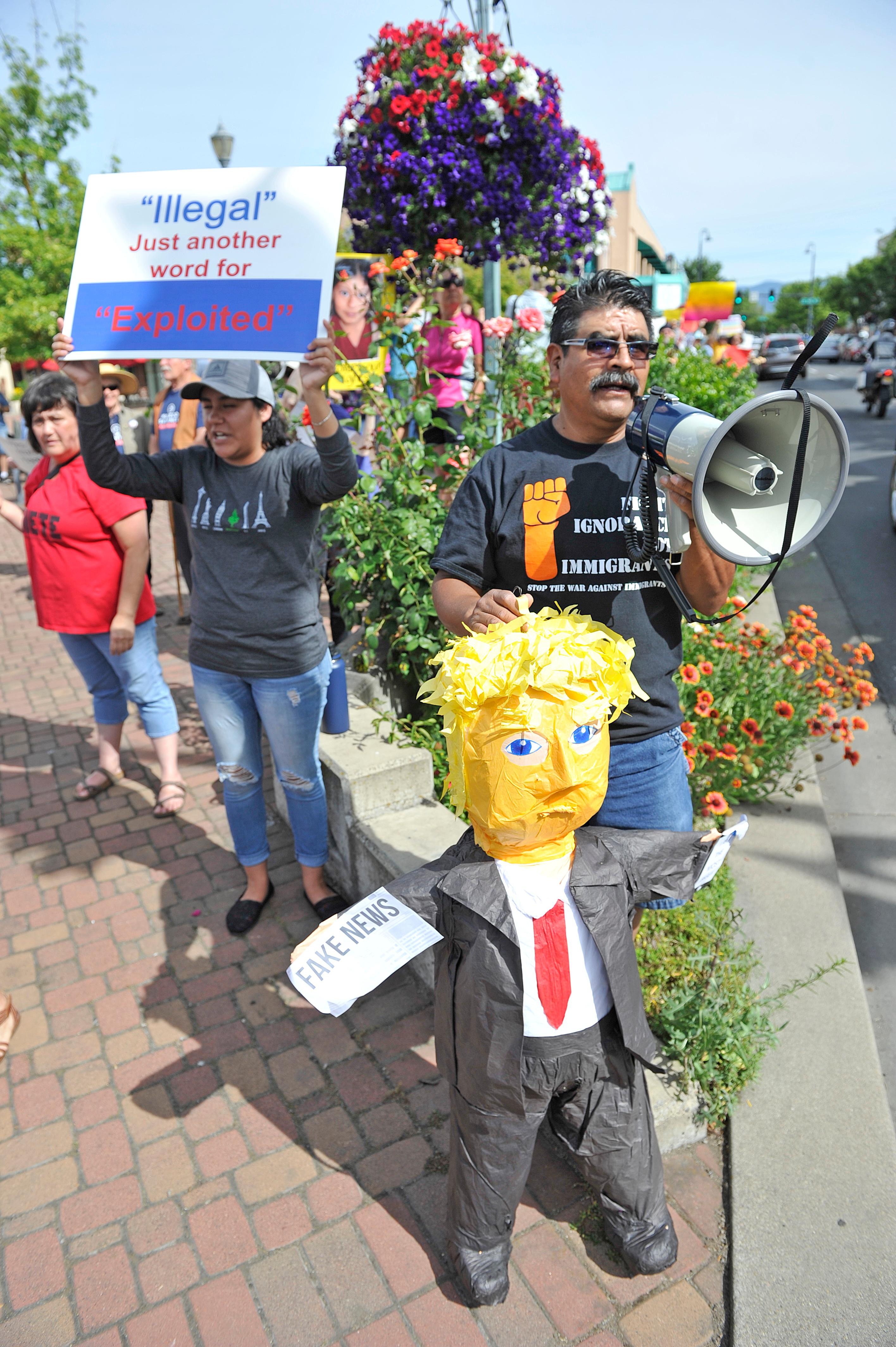 "Jamie Lusch / Mail Tribune{ } Dagoeerto Morles holds a trump piñata during the ""Where are the Children Rally"" at Vogule Plaza in Medford on Friday."