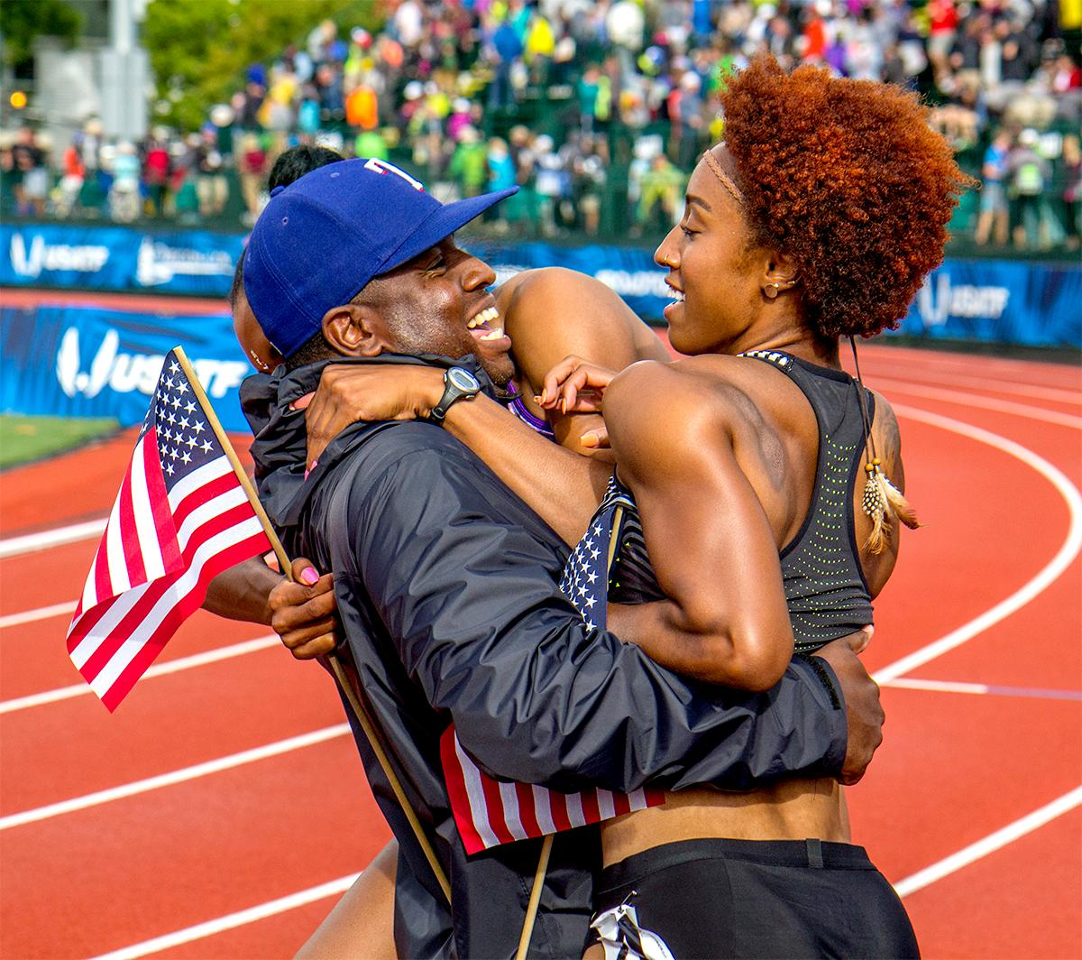 The coach of Brianna Rollins and Nia Ali runs up and embraces them after they took first and third in the 100 meter steeplechase. Photo by August Frank, Oregon News Lab