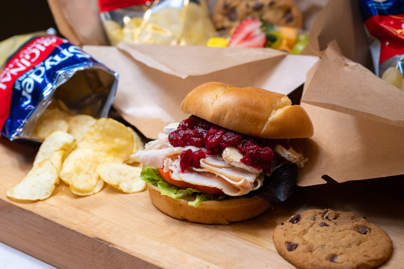 Their boxed lunches are available through the end of the year. Pictured: turkey and brie with cranberry compote, lettuce, and tomato on a brioche bun. Each boxed lunch comes with a bagged snack, cookie, and fruit salad. / Image: Phil Armstrong, Cincinnati Refined // Published: 11.6.20