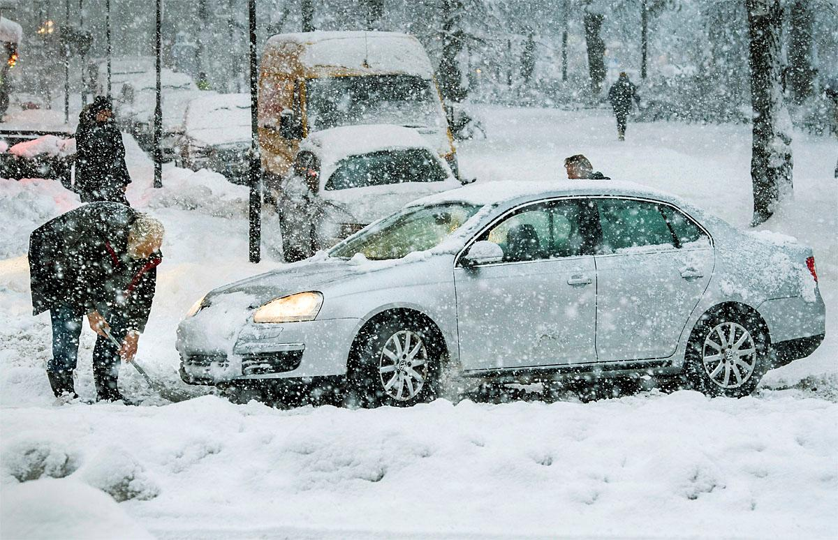 A man tries to dig out a car during  heavy snowfall in Stockholm, Wednesday, Nov. 9, 2016. All bus traffic was halted Wednesday and many main roads were blocked by trucks, buses and cars stuck in the snow. (Claude Bresciani/TT via AP)
