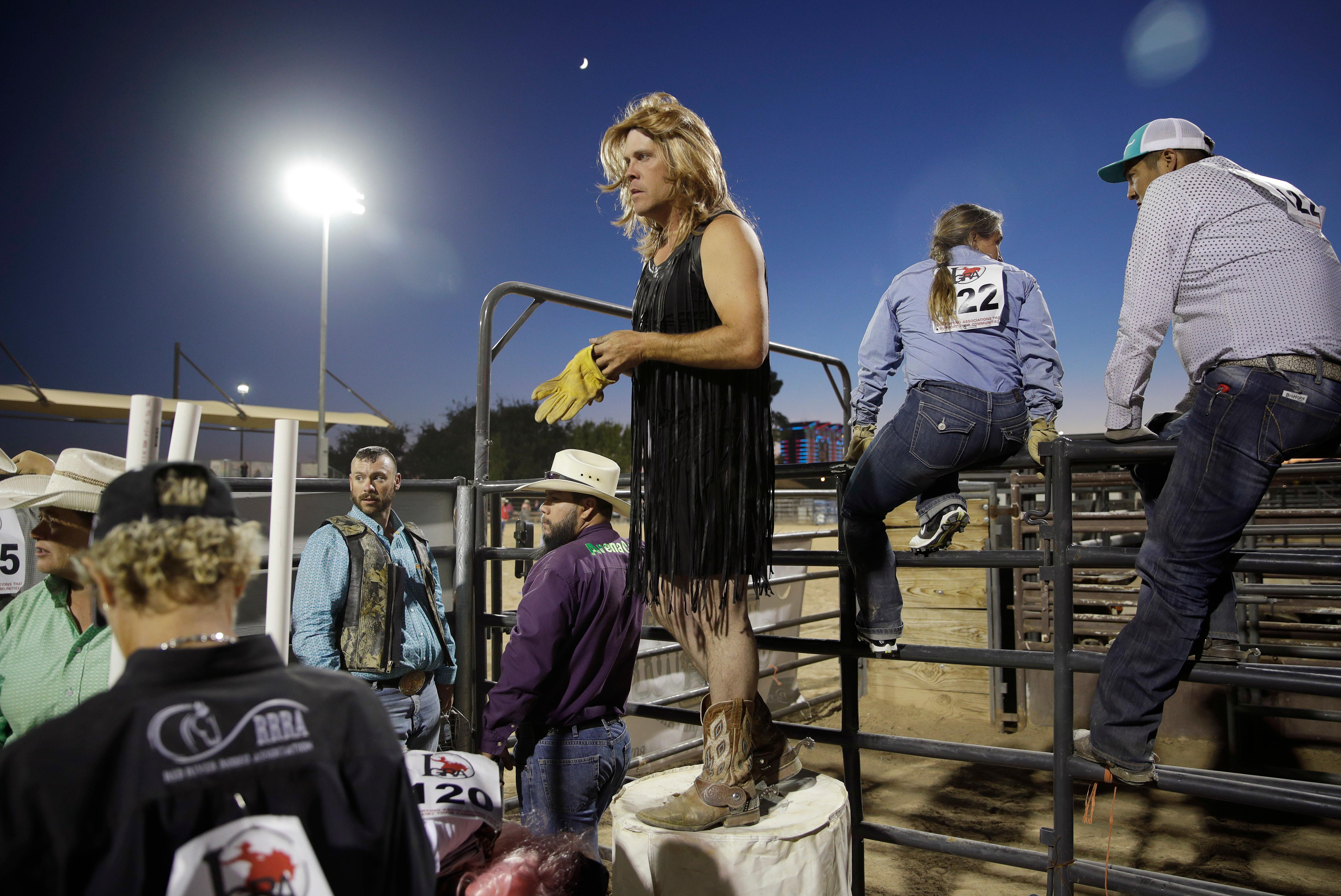 In this Sept. 24, 2017, photo, David Lawson, center, dons gloves before competing in the wild drag race event at the Bighorn Rodeo in Las Vegas. The event requires two competitors to control a steer while a third, dressed in drag, must ride the animal over a finish line. (AP Photo/John Locher)