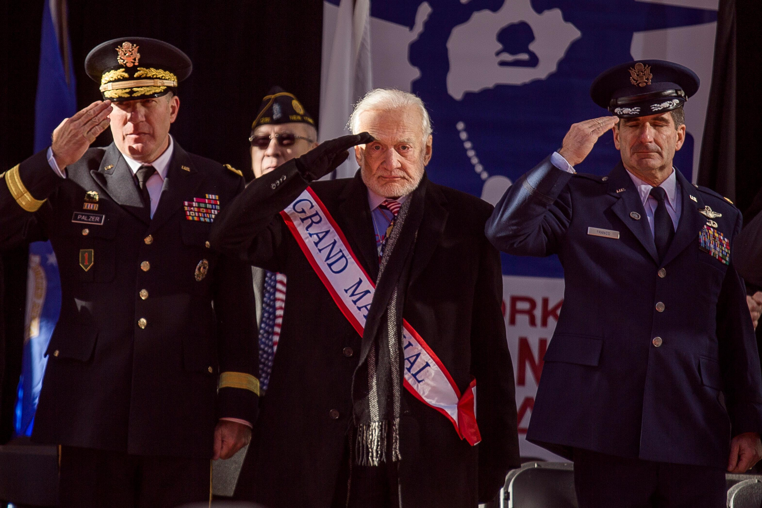 Former astronaut Buzz Aldrin, center,salutes during the annual Veterans Day parade in New York, Saturday, Nov. 11, 2017. Aldrin served as Grand Marshal as he joined Mayor Bill de Blasio and others at the city's parade. (AP Photo/Andres Kudacki)