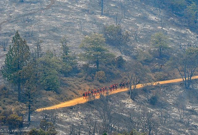 Jamie Lusch / Mail Tribune<br>Firefighters work their way up steep terrain off of Ditch Creek Road inside the Klamathon fire in California.