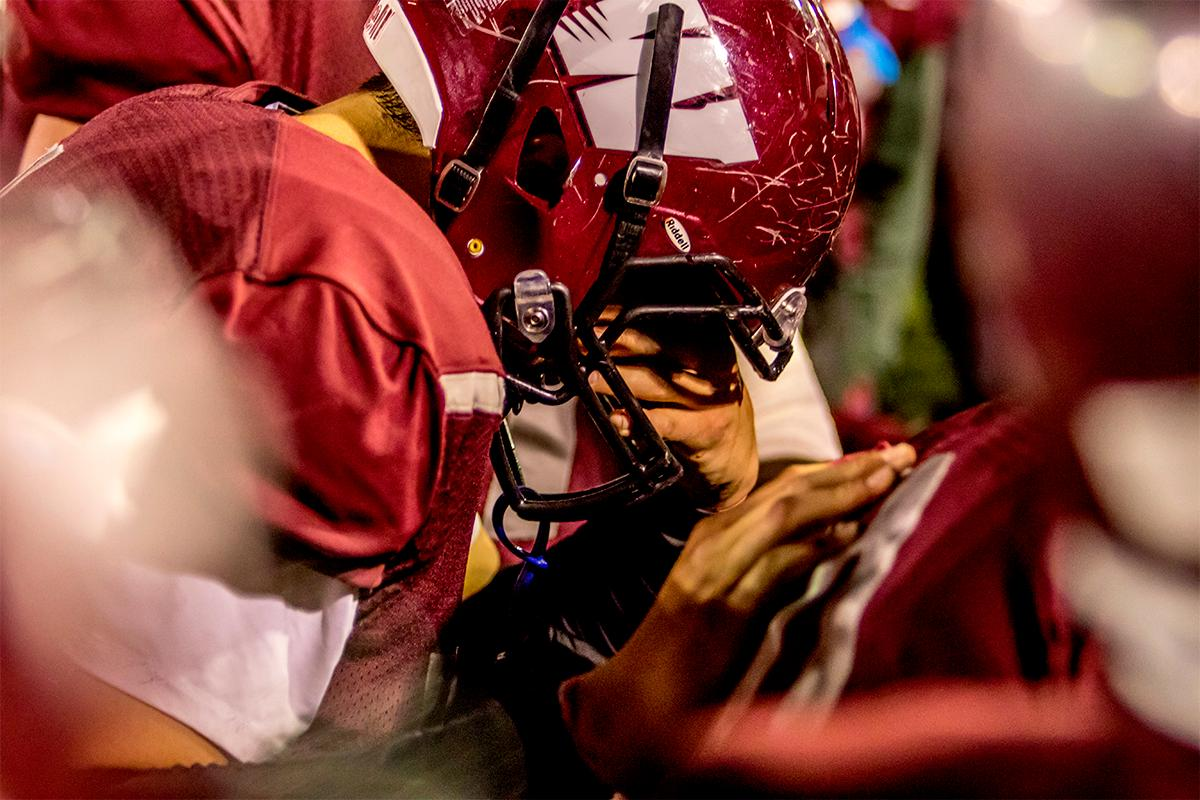 A Willamette player holds his head with teammates after suffering a loss to the Roseburg Indians 21-20 at Willamette on Friday. Photo by August Frank, Oregon News Lab
