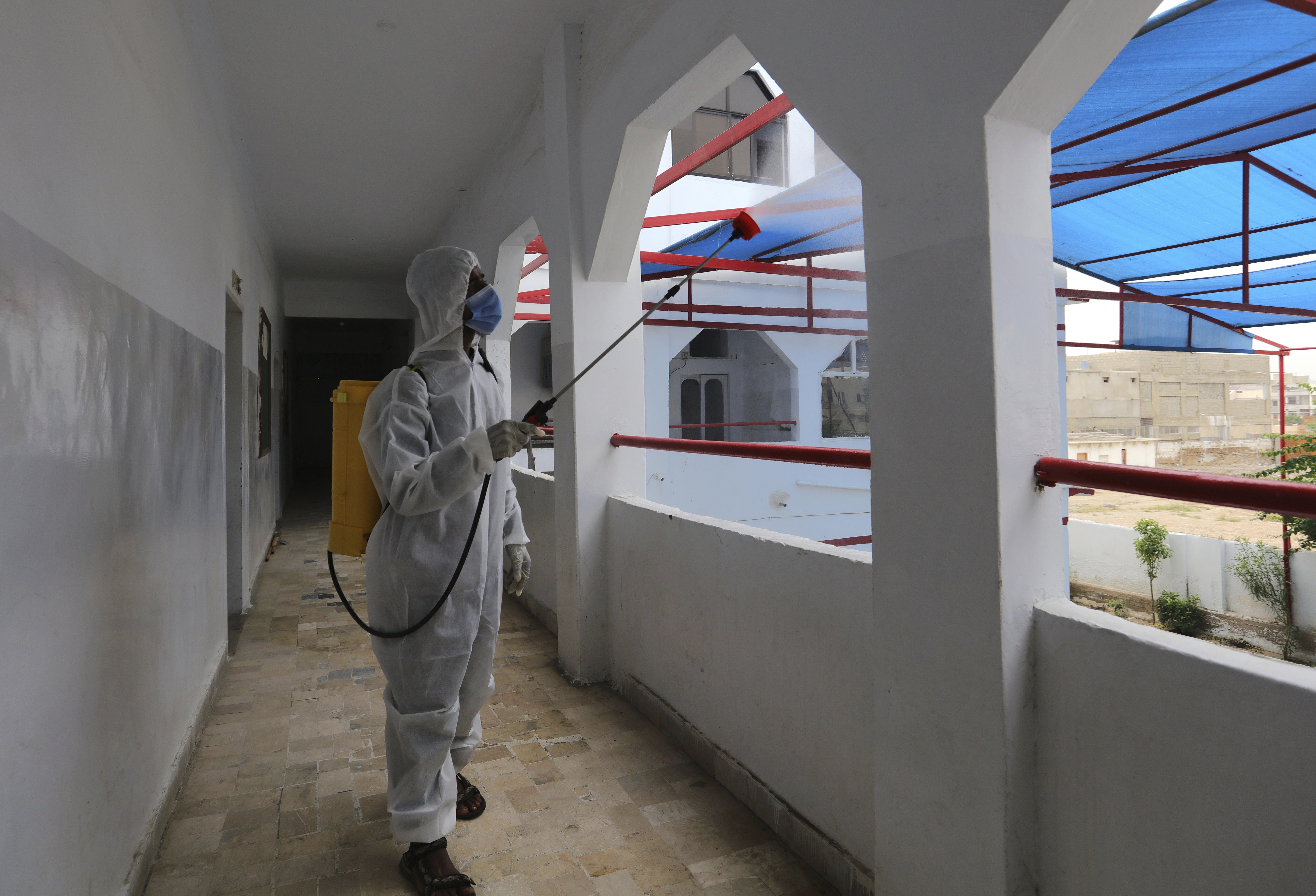 A worker sprays disinfectant in a school as preparation for reopening of educational institutions that were closed in March are finalized, in Karachi, Pakistan, Monday, Sept. 14, 2020. Education officials in Pakistan say authorities will start reopening educational institutions from Sept. 15 amid a steady decline in coronavirus deaths and infections. (AP Photo/Fareed Khan)