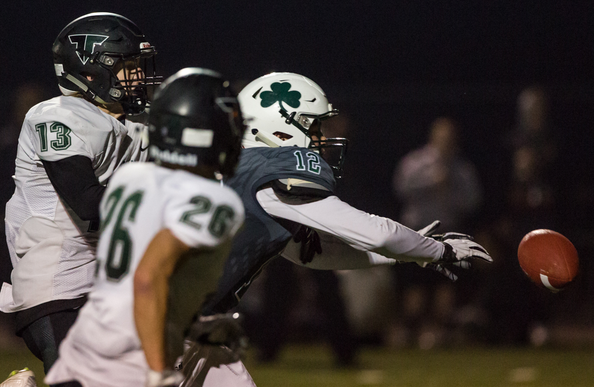 Sheldon Irish receiver Sam Olsson (#12) misses the ball by inches while under pressure from Tigard defensive back Zane Woodard (#13).  The Tigard Tigers defeated Sheldon 27-0 to advance to the OSAA 6A semifinals.  Photo by Austin Hicks, Oregon News Lab