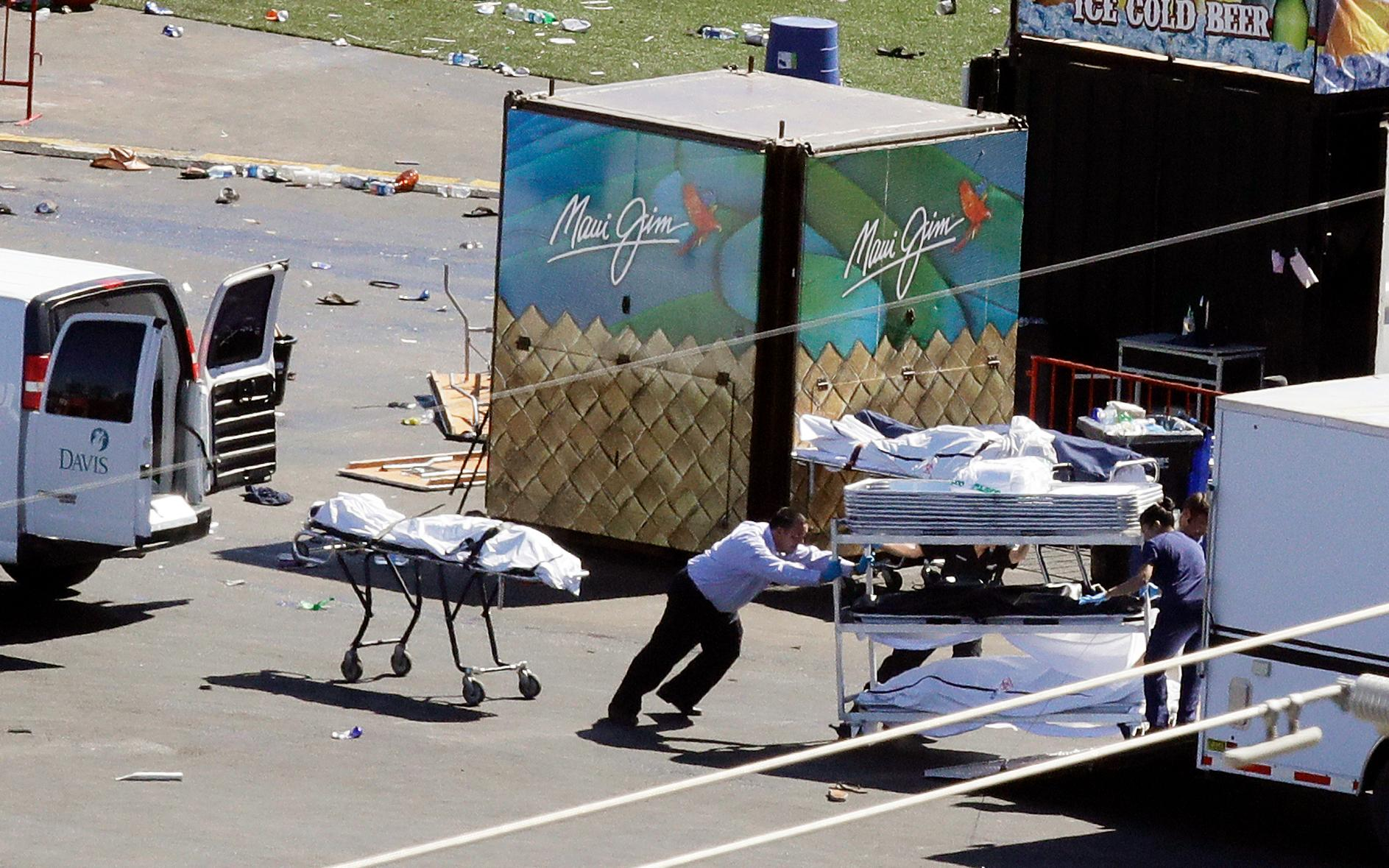 FILE--In this Oct. 2, 2017, file photo, investigators load bodies from the scene of a mass shooting at a music festival near the Mandalay Bay resort and casino on the Las Vegas Strip in Las Vegas. Two Nevada judges in Las Vegas have ordered the release of search warrant records and autopsy reports related to the deadliest mass shooting in modern U.S. history, with some information redacted.(AP Photo/Chris Carlson, file)