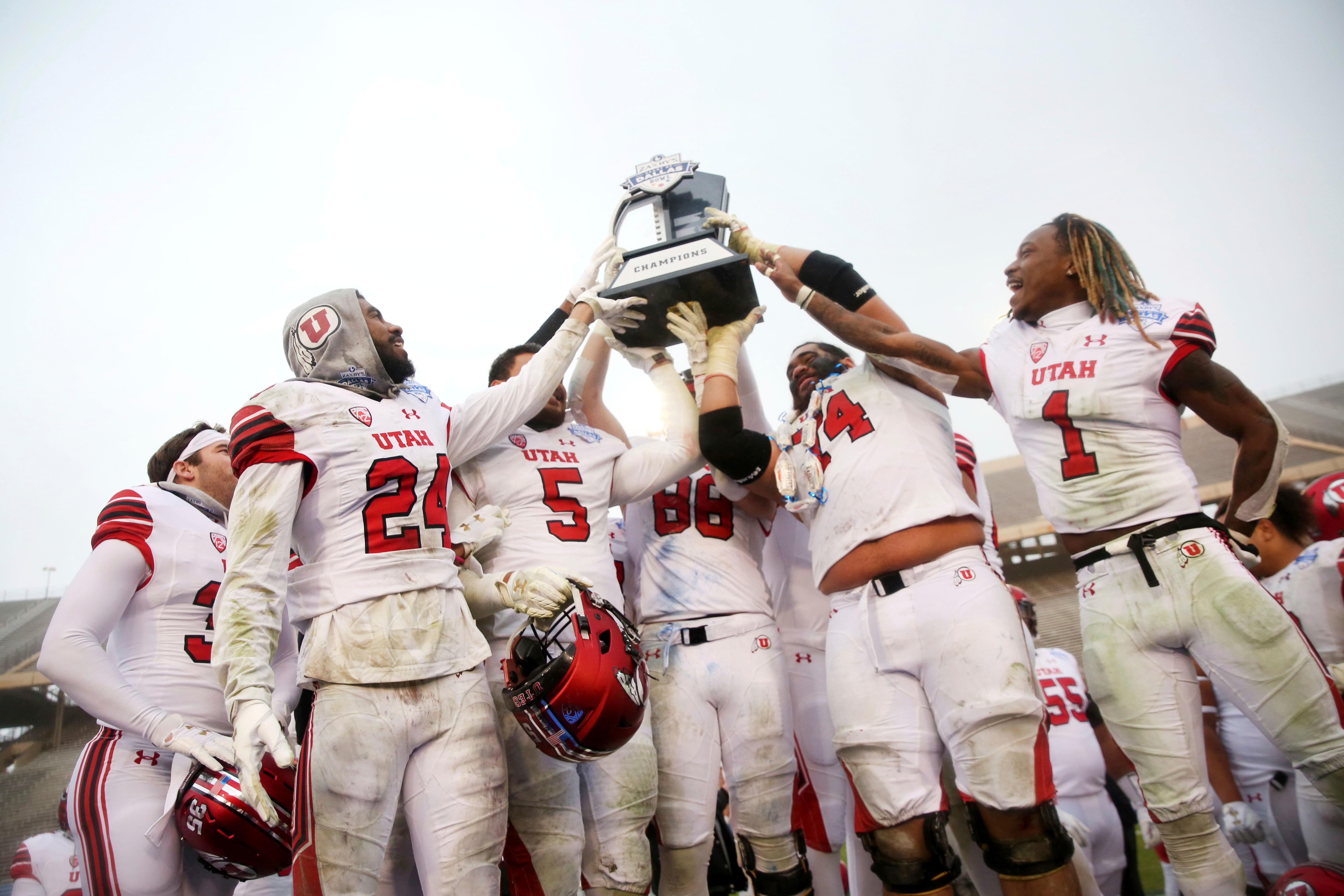 Utah football players hold up their championship trophy after winning the Zaxby's Heart of Dallas Bowl against West Virginia at Cotton Bowl Stadium in Dallas on Tuesday, Dec. 26, 2017. Utah won 30-14. (Rose Baca/The Dallas Morning News via AP)
