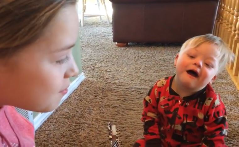 "Lydia Gray, 12, and Bo Gray, 2, sing ""You Are My Sunshine"" in a video posted yesterday that is gaining attention and unintended awareness to Down syndrome. (Photo: Amanda Gray / YouTube)"
