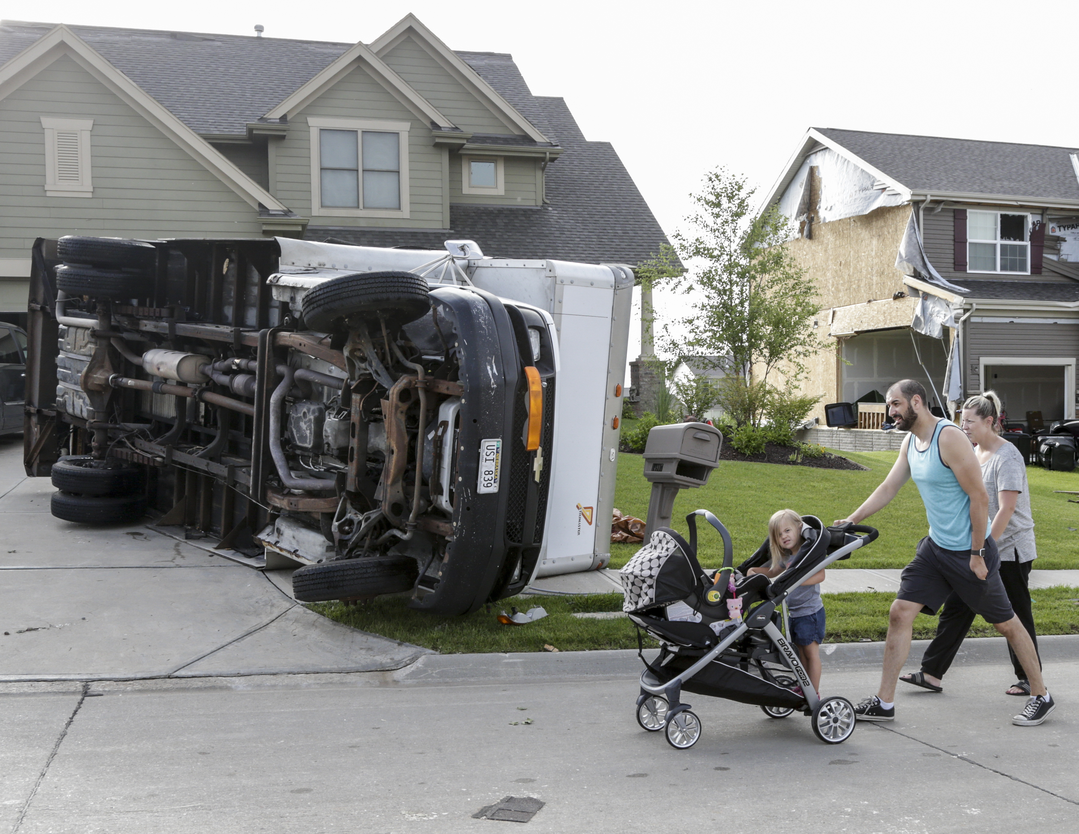 Vincent and Lindsey Mercado and their children walk past an overturned truck and weather damaged homes in the Hyda Hills neighborhood in Bellevue, Neb., Saturday, June 17, 2017. A severe weather front passed through the area the previous evening. (AP Photo/Nati Harnik)