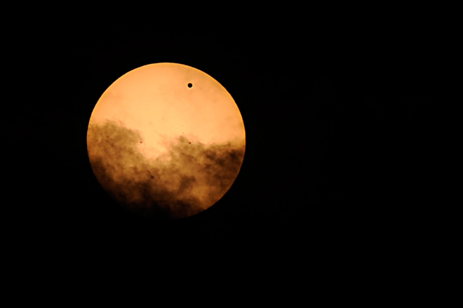 The small black dot seen at the top right of the sun is the planet Venus, as it transits across the face of the sun Tuesday, June 5, 2012, as seen from Mt. Trashmore in Virginia Beach, Va. The next transit of Venus won't be for another 105 years. (AP Photo/Virginian-Pilot, Amanda Lucier)