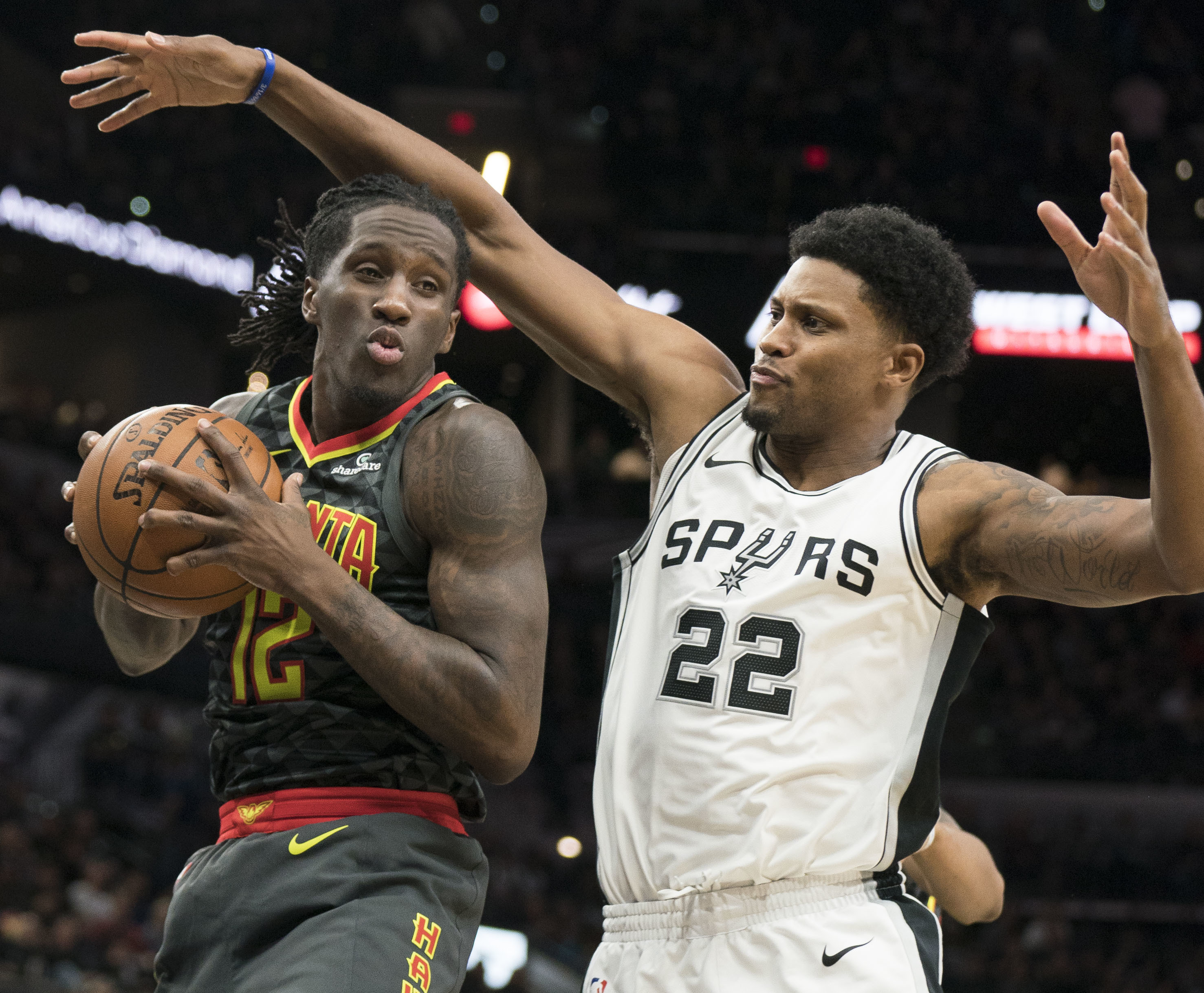 Atlanta Hawks forward Taurean Prince (12) looks to pass as he is guarded by San Antonio Spurs forward Rudy Gay during the first half of an NBA basketball game, Monday, Nov. 20, 2017, in San Antonio. (AP Photo/Darren Abate)