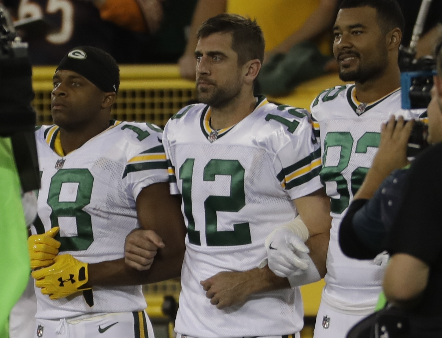 Green Bay Packers' Aaron Rodgers links arms with Richard Rodgers and Randall Cobb during the national anthem before an NFL football game against the Chicago Bears Thursday, Sept. 28, 2017, in Green Bay, Wis. (AP Photo/Morry Gash)